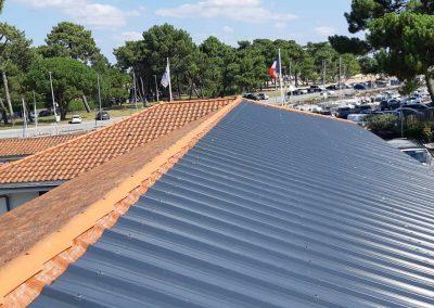 Vue du rendu du bac acier d'une toiture de l'école du Betey avant pose des panneaux, avec en fond le port du Betey